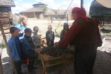 Bondurant School children learn about blacksmithing from Veni Musumecci during Living History Days at the Museum of the Mountain Man.